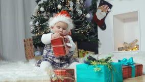 Il piccolo bambino si siede in un cappuccio Santa con un regalo stock footage