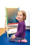 Il piccolo bambino sta disegnando con il gesso di colore sul bordo di gesso Fotografia Stock
