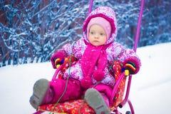 Il piccolo bambino sta guidando su una slitta nell'inverno Fotografia Stock Libera da Diritti
