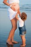 Il piccolo bambino sta tenendo la pancia della madre incinta Immagini Stock Libere da Diritti