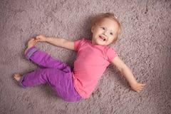Il piccolo bambino sveglio sta rilassandosi sulla pavimentazione Fotografia Stock Libera da Diritti