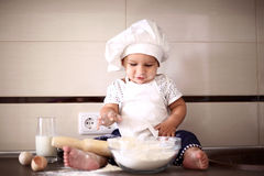 Il piccolo bambino sveglio in una protezione del cuoco ride Fotografia Stock Libera da Diritti