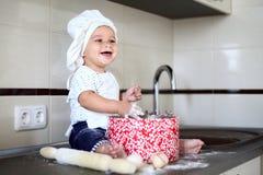 Il piccolo bambino sveglio in una protezione del cuoco ride Immagini Stock Libere da Diritti