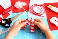 Il piccolo bambino tiene il bastoncino di zucchero del feltro di Natale in sue mani Rifornimenti di cucito per fare le decorazion Fotografia Stock Libera da Diritti