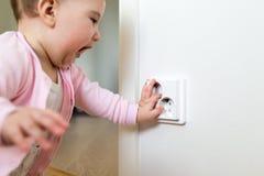 Il piccolo bambino tocca uno sbocco elettrico a casa Sicurezza dei bambini fotografia stock libera da diritti