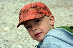 Il piccolo bambino in una protezione osserva con interesse Immagine Stock