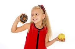 Il piccolo bello bambino biondo che scelgono il dessert che tiene la ciambella non sana del cioccolato e la mela fruttificano Fotografia Stock Libera da Diritti