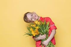 Il piccolo bello bambino con la camicia rosa dà un mazzo dei tulipani il giorno del ` s delle donne, il giorno del ` s della madr Immagine Stock Libera da Diritti
