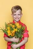 Il piccolo bello bambino con la camicia rosa dà un mazzo dei tulipani il giorno del ` s delle donne, il giorno del ` s della madr Fotografia Stock Libera da Diritti