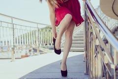 Il piccolo breve abbigliamento rosso troppo grande si spoglia il concetto elegante di lusso Chiuda sulla foto di signora stanca e fotografia stock