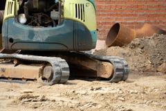 Il piccolo caricatore del cingolo scava nella fossa del parco per posare i tubi fotografia stock