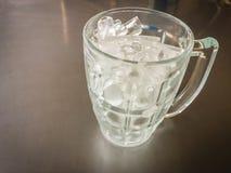Il piccolo cilindro ha modellato di ghiaccio nella brocca di vetro messa sull'acciaio t Fotografia Stock Libera da Diritti