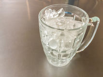 Il piccolo cilindro ha modellato di ghiaccio nella brocca di vetro messa sull'acciaio t Immagine Stock