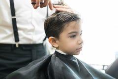Il piccolo cliente sta ottenendo il taglio di capelli dal parrucchiere At Barber Shop immagini stock libere da diritti
