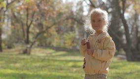 Il piccolo colpo biondo sveglio della ragazza bolle in parco video d archivio