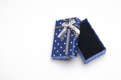 Il piccolo contenitore di regalo blu aperto con il nastro ed i cerchi completano Fotografia Stock