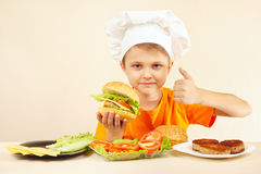 Il piccolo cuoco unico divertente espressivo gode dell'hamburger cucinato Immagini Stock