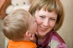 Il piccolo figlio bacia la sua mamma Immagini Stock