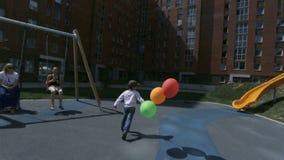 Il piccolo figlio delle madri funziona con i palloni variopinti sulla via stock footage