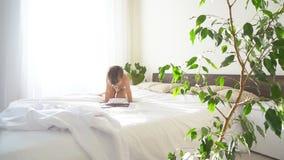 Il piccolo figlio si trova sul letto nella camera da letto ed esamina la compressa di Internet archivi video