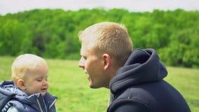 Il piccolo figlio sveglio dà al padre il dente di leone giallo in parco stock footage
