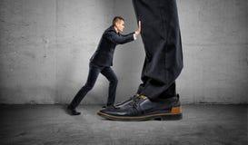Il piccolo imprenditore sta spingendo un ` s del grande capo piedi enormi su fondo grigio Immagini Stock Libere da Diritti