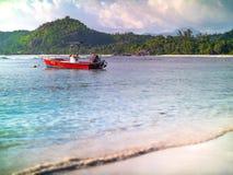 Il piccolo motoscafo rosso si è ancorato fuori dall'le Seychelles tira su y soleggiato Immagini Stock Libere da Diritti