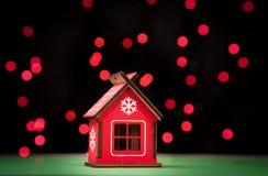 Il piccolo Natale rosso del giocattolo si dirige, contro lo sfondo delle palle sopportate rosse Fotografia Stock