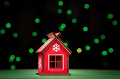 Il piccolo Natale rosso del giocattolo si dirige, contro lo sfondo delle palle sopportate verdi Immagini Stock