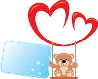 Il piccolo orsacchiotto che si siede su un'oscillazione di due cuori e tiene nella zampa della cartolina d'auguri Immagine Stock