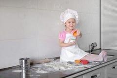 Il piccolo panettiere sorridente della neonata nel cappello e nel grembiule bianchi del cuoco impasta una pasta sulla cucina di t fotografia stock libera da diritti