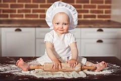 Il piccolo panettiere sorridente della neonata nel cappello e nel grembiule bianchi del cuoco impasta una pasta Fotografia Stock