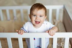 Il piccolo piccolo ragazzo biondo adorabile sveglio in un bodykit a strisce è dentro Fotografie Stock Libere da Diritti