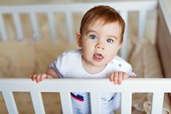 Il piccolo piccolo ragazzo biondo adorabile sveglio in un bodykit a strisce è dentro Fotografia Stock Libera da Diritti