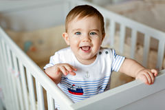 Il piccolo piccolo ragazzo biondo adorabile sveglio in un bodykit a strisce è dentro Immagine Stock Libera da Diritti
