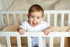 Il piccolo piccolo ragazzo biondo adorabile sveglio in un bodykit a strisce è dentro Fotografie Stock