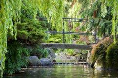 Il piccolo ponte pedonale dietro il fogliame verde degli alberi, i cespugli e le rocce sopra un'insenatura/corrente in Beacon Hil Fotografia Stock Libera da Diritti
