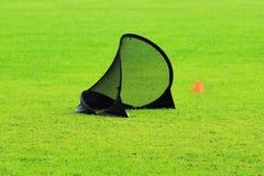 Il piccolo portone di calcio per la formazione scherza agli sport calcio ed al limitatore della plastica in uno stadio con l'erba Fotografie Stock Libere da Diritti
