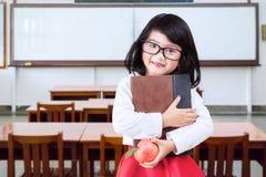 Il piccolo principiante tiene il libro e la mela nella classe Immagini Stock
