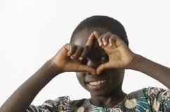 Il piccolo ragazzo africano fa un gesto di mano mentre sorridendo, isolato immagine stock libera da diritti