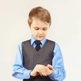 Il piccolo ragazzo alla moda ha fissato i bottoni sulla camicia del blu della manica Immagini Stock