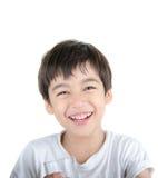 Il piccolo ragazzo asiatico beve l'acqua da un vetro su fondo bianco Immagine Stock