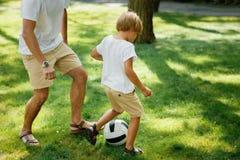 Il piccolo ragazzo biondo che dura nella maglietta bianca e mette il footboll in cortocircuito plaing con suo padre sul prato ing immagini stock