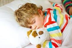 Il piccolo ragazzo biondo del bambino in indumenti da letto variopinti copre il sonno Immagine Stock