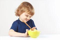 Il piccolo ragazzo biondo sveglio rifiuta di mangiare il cereale Fotografia Stock