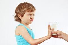 Il piccolo ragazzo biondo sveglio rifiuta il latte fresco della bevanda Fotografia Stock Libera da Diritti