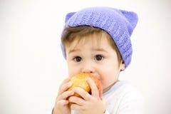Il piccolo ragazzo caucasico sveglio 11 mese si siede e mangia la mela rossa su fondo bianco Immagini Stock