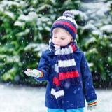 Il piccolo ragazzo divertente sveglio nell'inverno variopinto copre divertiresi con fotografie stock libere da diritti