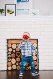Il piccolo, ragazzo divertente un anno di nascita tiene in suoi fiori artificiali rossi delle mani sui precedenti di un camino Immagini Stock Libere da Diritti