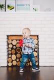 Il piccolo, ragazzo divertente un anno di nascita tiene in suoi fiori artificiali rossi delle mani sui precedenti di un camino Fotografie Stock